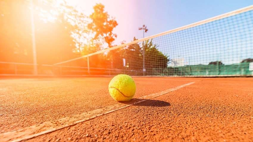 Tennis ball sitting on a court on a sunny day
