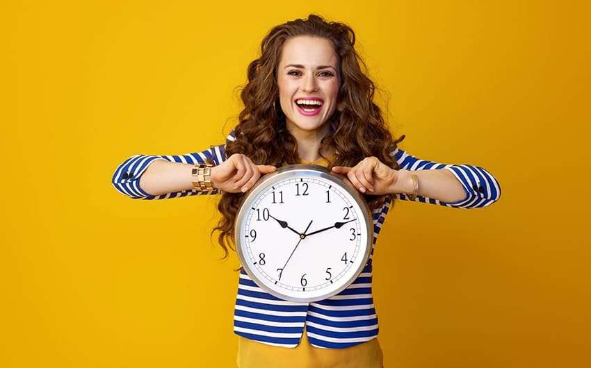 Attractive, stylish woman against a yellow background shows off her smile and a large clock. If you're toying with the idea of braces or perhaps one of your children need braces, you might wonder when the best time to get braces is.