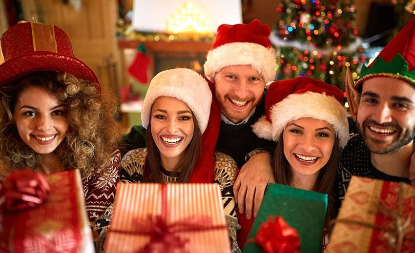 A group of smiling people at Christmas. Get your smile ready for the busy holiday season with a professional whitening treatment at Palencia Dental.