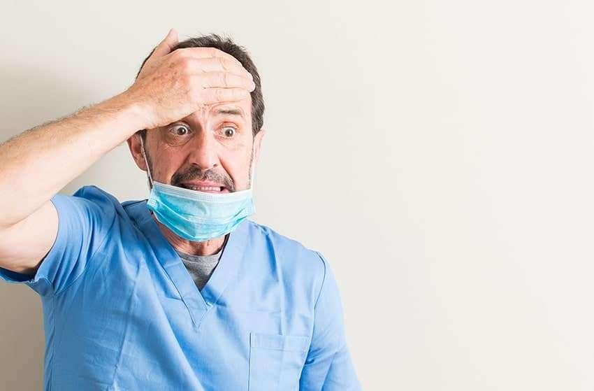 Dentist with a headache holds his head