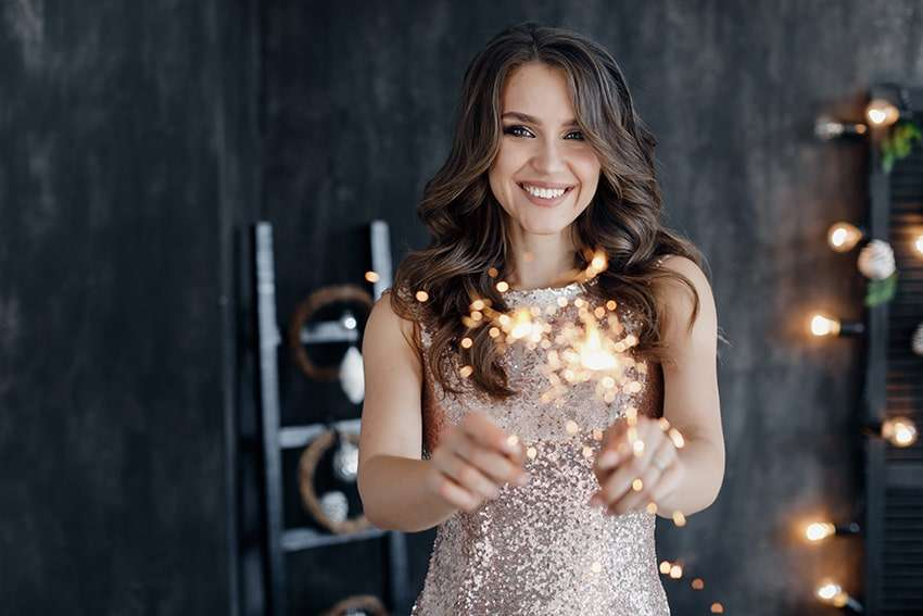 Attractive young woman stands in a beautiful evening dress on New Years with sparklers