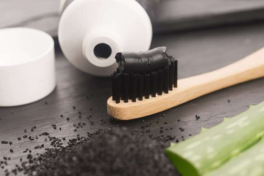 Toothbrush with black charcoal toothpaste sitting on a countertop