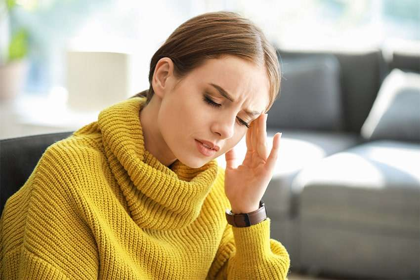 woman in yellow turtle neck suffering from headache